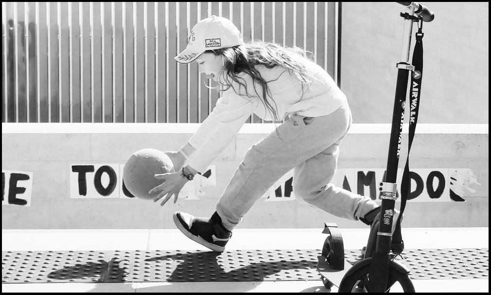 Saisissez la balle au bond! Une petite fille se saisie d'un ballon rebondissant.